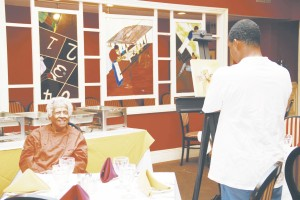 Leah Chase posing for a portrait by artist Gustave Blache at Dooky Chase Restaurant. The oil portrait appears in the artist's book, Dooky Chase Restaurant Featuring Leah Chase.