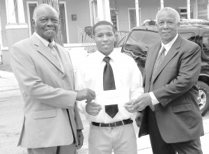 Scholarship recipient, Joseph Parker is flanked by the Rev. Johnny McKinnies and Joseph L. Williams, who presented Parker with his scholarship.