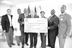 On hand for the check presentation to The Network for Community Opportunity from Wells Fargo, are from left: Councilman Jared Brossett, Henry Baptiste of New Orleans East Hospital, Councilman James Gray, Mayor Mitch Landrieu, Ashleigh Gardere, executive director of the Network for Economic Opportunity; Hugh Rowden of Wells Fargo, and Mario Garner, CEO of New Orleans East Hospital. Photo courtesy of the City of New Orleans