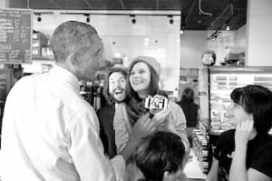 President Obama looks at a selfie with restaurant staff at Charmington's Café in North Baltimore, Md., on Jan. 15. The president stopped at the restaurant to promote his proposal to guarantee paid sick leave for American workers.  (Pete Souza/The White House