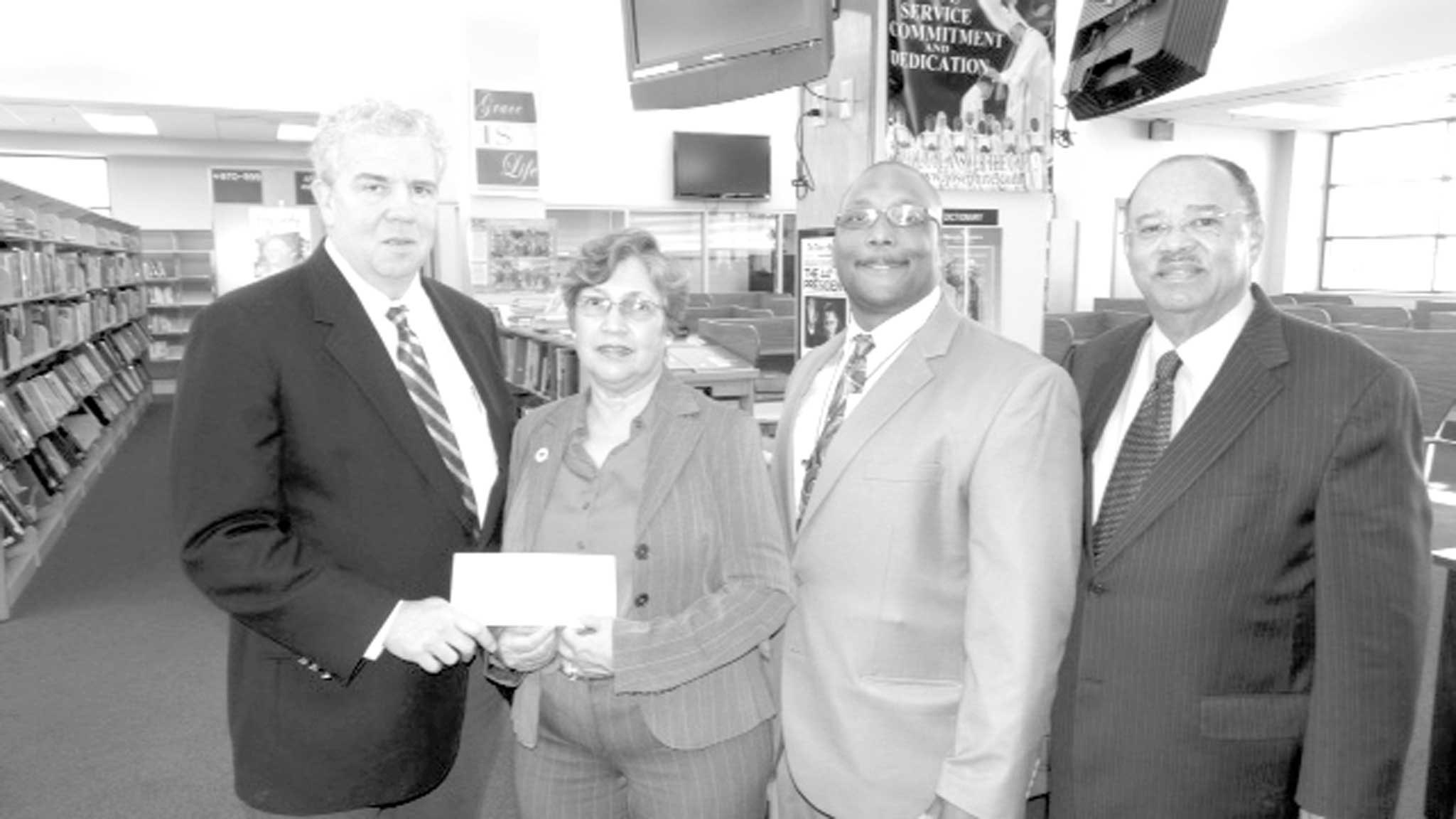 Making the corporate donation on behalf of AT&T to Ladies for Purple Scholars Foundation representative Ann Eugene is Leo Marsh, left. On hand for the presentation are St. Aug principal Sean Goodwin, second from right, and Lambert Boissiere, Constable of First City Court and St. August alumnus.