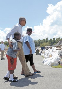 President Barack Obama walks with a family to our their flood-damaged home in the Castle Place neighborhood of Baton Rouge, La., Aug. 23, 2016.