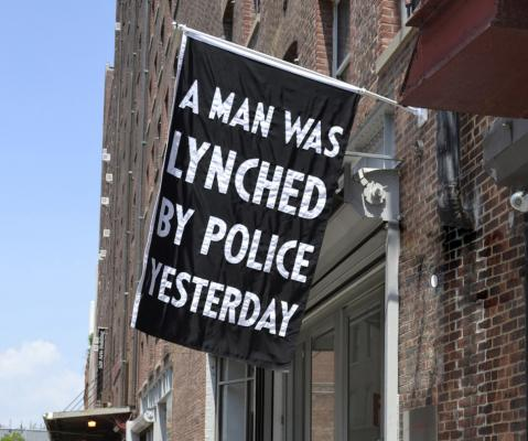 "Dread Scott's flag, ""A Man Was Lynched By Police Yesterday,"" on view at Jack Shainman Gallery (2016). Photo courtesy of the artist and Jack Shainman Gallery."
